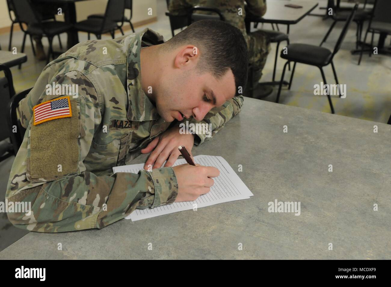 Mississippi Army National Guard Spc. Don N. Kazery, Joint Force Headquarters, takes an exam during the opening event of the Mississippi Best Warrior Competition Feb. 26, 2018. The Best Warrior Competition highlights the various skills and expertise our Soldiers and Airmen contribute to the National Guard team and our all-volunteer force. (U.S. National Guard photo by Chelsy Ables) - Stock Image
