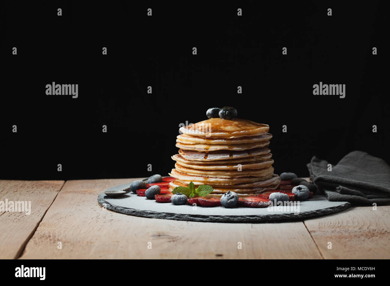 Front view of Stack of homemade plain pancakes with strawberries, blueberries and maple syrup served on black plate on black background with selective - Stock Image