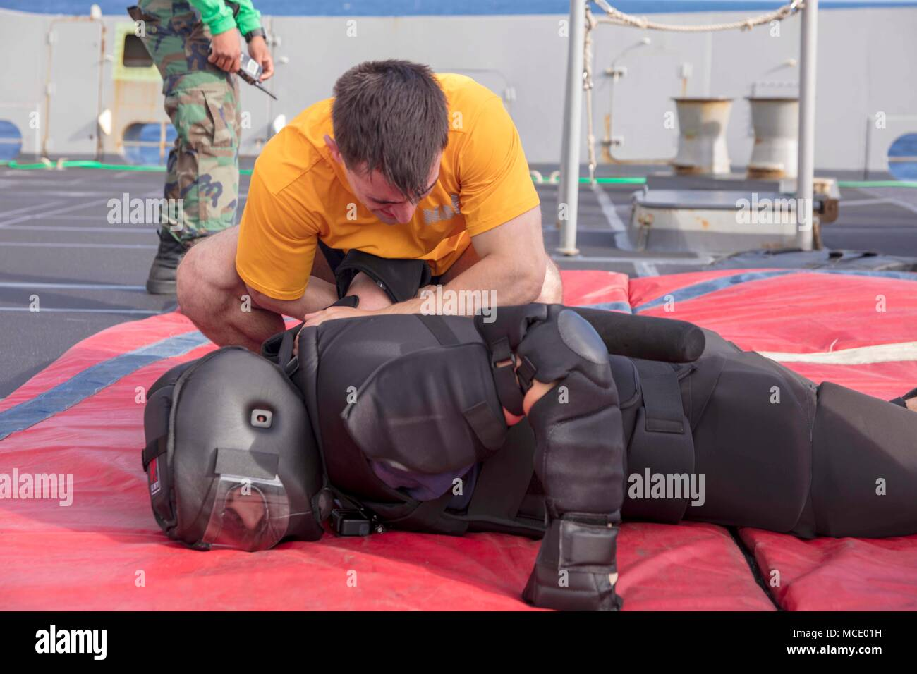 180223-N-GR168-0287 ATLANTIC OCEAN (Feb. 23, 2018) Ensign Dane Kozlosky, from Mantua, New Jersey, performs a mechanical ddvantage controlled hold take-down on Lt. Andrew Spilling, from St. Louis, during security reaction force basic training on the fo'c'sle of the San Antonio-class amphibious transport dock ship USS New York (LPD 21) Feb. 23, 2018. New York, homeported in Mayport, Florida, is conducting naval operations in the U.S. 6th Fleet area of operations. (U.S. Navy photo by Mass Communication Specialist 2nd Class Lyle Wilkie/Released) - Stock Image