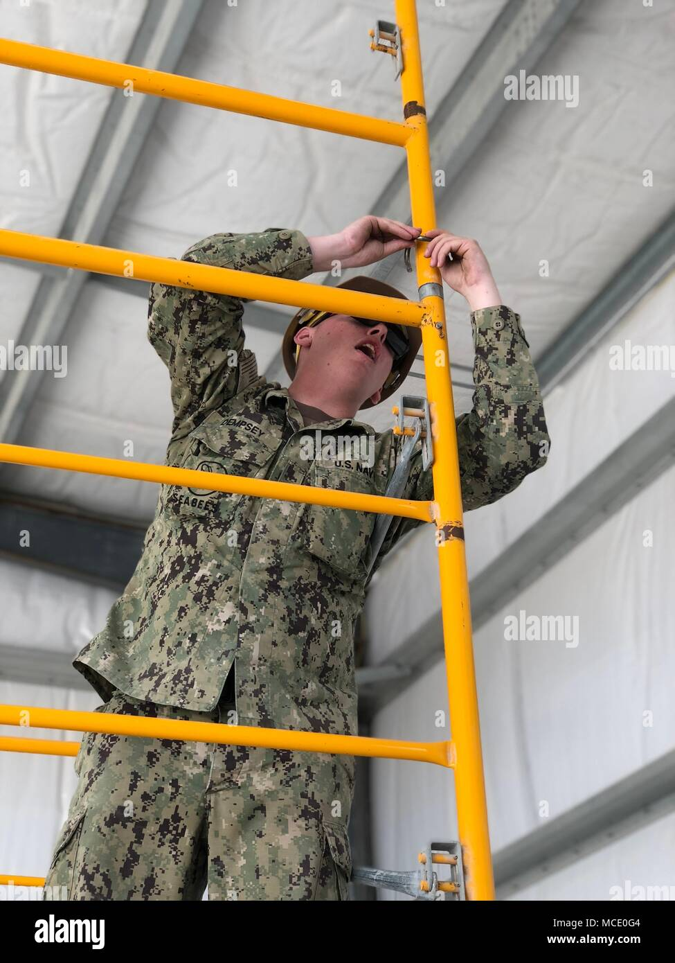 Builder Constructioman Andrew Dempsey, a Seabee assigned to Naval Mobile Construction Battalion (NMCB) 11, helps assemble scaffolding for rollup door installation in the alpha pre-engineered building. NMCB 11 is homeported in Gulfport, Mississippi, and is part of the Naval Construction Force (NCF). They currently have personnel assigned to more than 15 locations world-wide, performing a variety of missions in support of the Navy and the Department of Defense. Stock Photo