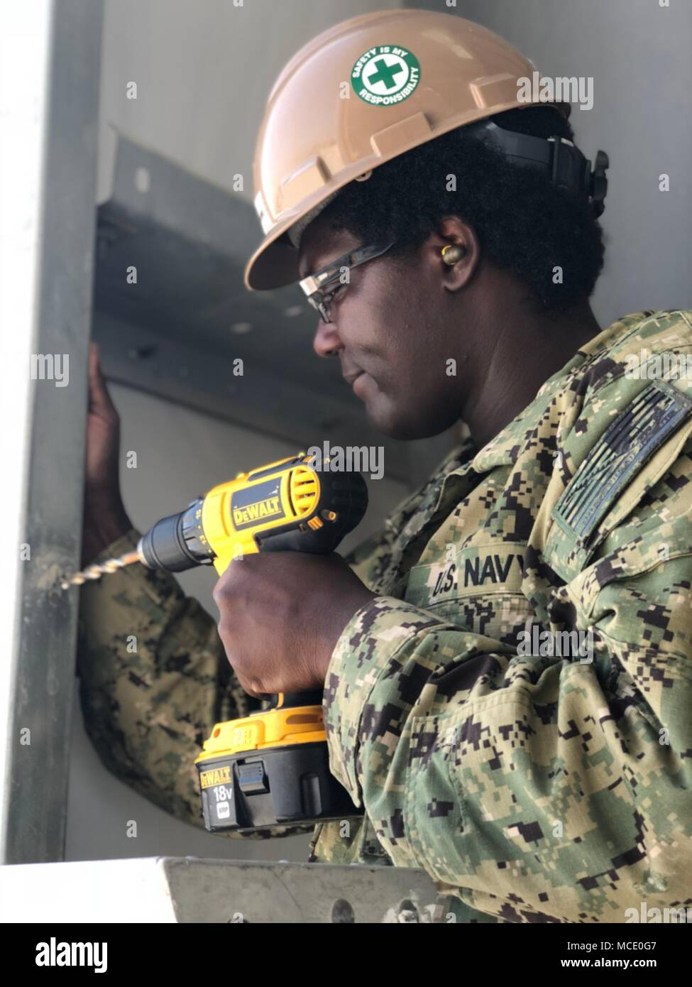 Utilitiesman 3rd Class LaToya Graham drills bolt sized holes to install a track for a roll up door to be installed in a alpha pre-engineered building. NMCB 11 is homeported in Gulfport, Mississippi, and is part of the Naval Construction Force (NCF). They currently have personnel assigned to more than 15 locations world-wide, performing a variety of missions in support of the Navy and the Department of Defense. Stock Photo