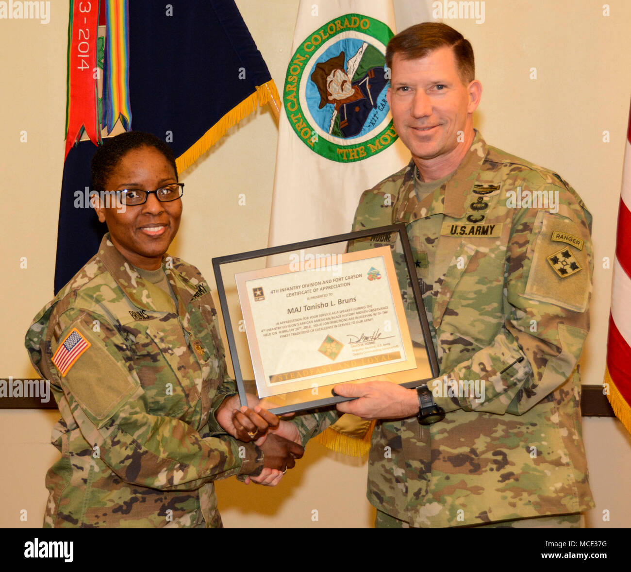 FORT CARSON, Colorado - Brig. Gen, Dave Hodne, Deputy Commanding General, 4th Infantry Division, presents Maj.Tanisha Bruns, the Clinical Nurse OIC for the Iron Horse Clinic, a Certificate of Appreciation for being a guest speaker during the African American/Black History Month at the Elkhorn Conference Center Feb. 26, 2018. (U.S. Army photo by Staff Sgt. Daniel Wyatt) - Stock Image