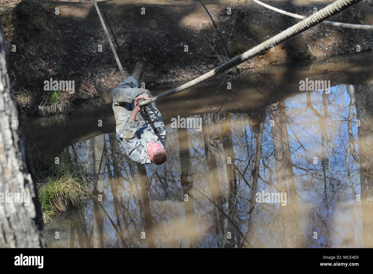 Tech Sgt. Thomas Rushing, of the 186th Air Refueling Wing in Meridian, Miss., crosses a rope bridge during the confidence course portion of the Mississippi National Guard 2018 Best Warrior Competition at the Camp McCain Training Center near Elliott, Miss., Feb. 27, 2018. (U.S. National Guard photo by Chelsy Ables) - Stock Image