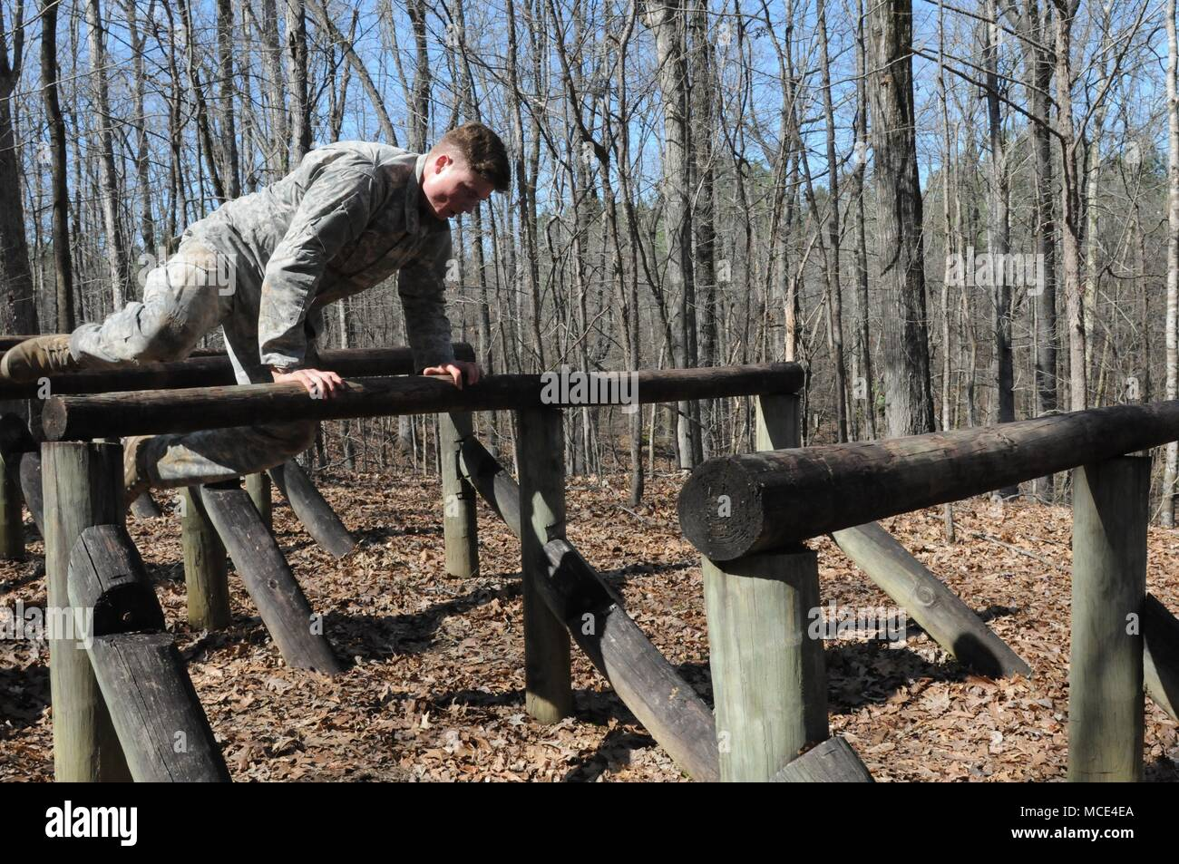 Sgt. Ethan Scott, of the 155th Armored Brigade Combat Team headquartered in Tupelo, Miss., jumps over log beams during the confidence course portion of the Mississippi National Guard 2018 Best Warrior Competition at the Camp McCain Training Center near Elliott, Miss., Feb. 27, 2018. (U.S. National Guard photo by Chelsy Ables) - Stock Image