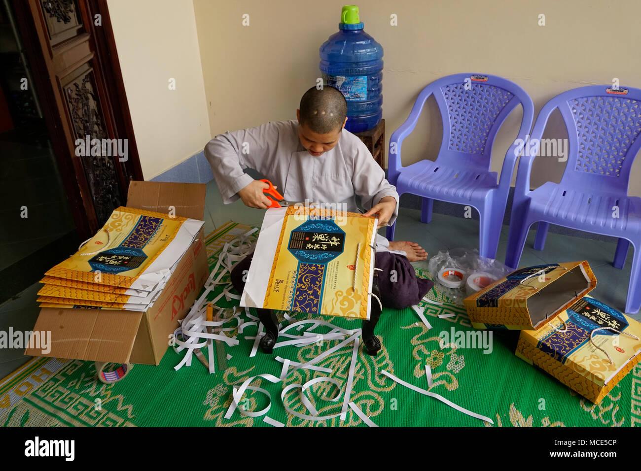 Monk working on making bags, Chùa Thiên Hòa temple, Nha Trang, Vietnam - Stock Image