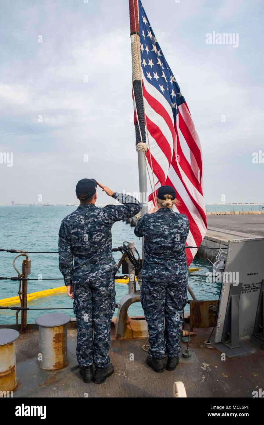 180218-N-DO281-0052  MANAMA, Bahrain (Feb. 18, 2018) Seaman Jacob Stricklin, left, salutes as Hospital Corpsman 2nd Class Sarah Harrell raises the national ensign during morning colors aboard the guided-missile cruiser USS Monterey (CG 61). Monterey is deployed to the U.S. 5th Fleet area of operations in support of maritime security operations to reassure allies and partners and preserve the freedom of navigation and the free flow of commerce in the region. (U.S. Navy photo by Mass Communication Specialist Seaman Trey Fowler/Released) Stock Photo