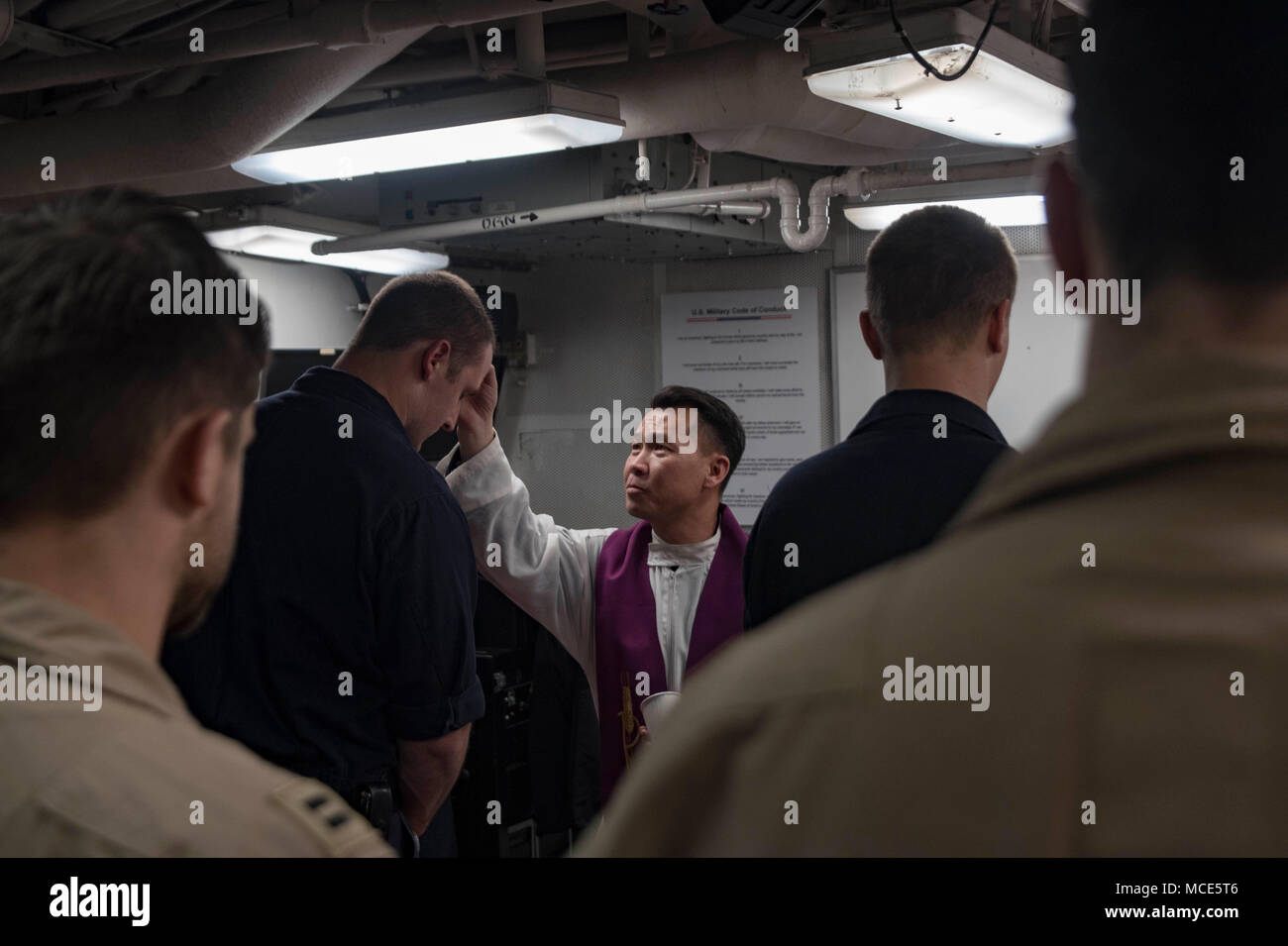 180214-N-DO281-1234  ARABIAN GULF (Feb. 14, 2018) Lt. Long Nguyen, a chaplain assigned to the aircraft carrier USS Theodore Roosevelt (CVN 71), blesses Interior Communications Electrician 1st Class Travis Coakley during an Ash Wednesday service aboard the guided-missile cruiser USS Monterey (CG 61). Monterey is deployed to the U.S. 5th Fleet area of operations in support of maritime security operations to reassure allies and partners and preserve the freedom of navigation and the free flow of commerce in the region. (U.S. Navy photo by Mass Communication Specialist Seaman Trey Fowler/Released) Stock Photo