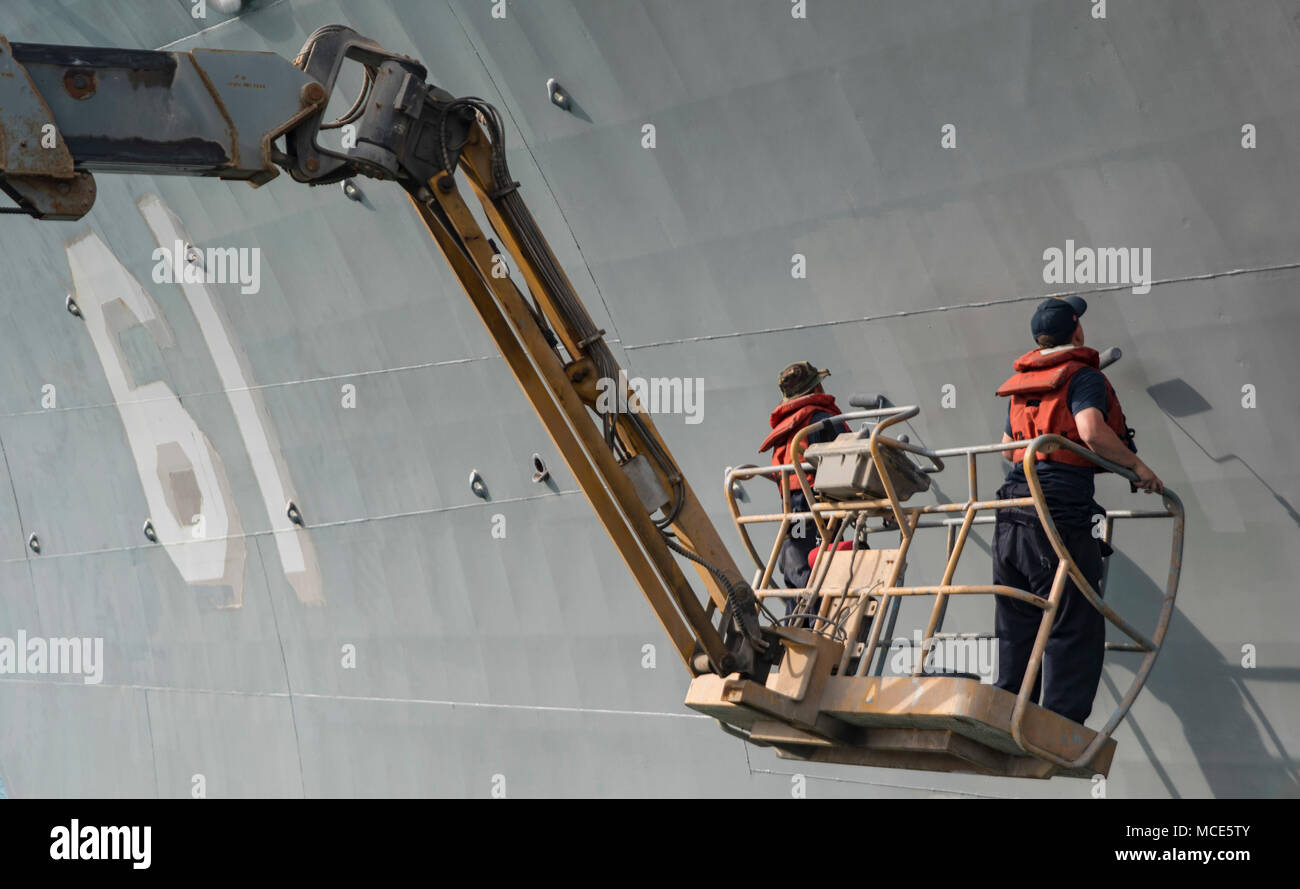 180218-N-DO281-0104  MANAMA, Bahrain (Feb. 18, 2018) Boatswain's Mate 2nd Class Paul Landsittel, left, and Seaman Aron Harrelson paint the side of the guided-missile cruiser USS Monterey (CG 61). Monterey is deployed to the U.S. 5th Fleet area of operations in support of maritime security operations to reassure allies and partners and preserve the freedom of navigation and the free flow of commerce in the region. (U.S. Navy photo by Mass Communication Specialist Seaman Trey Fowler/Released) Stock Photo