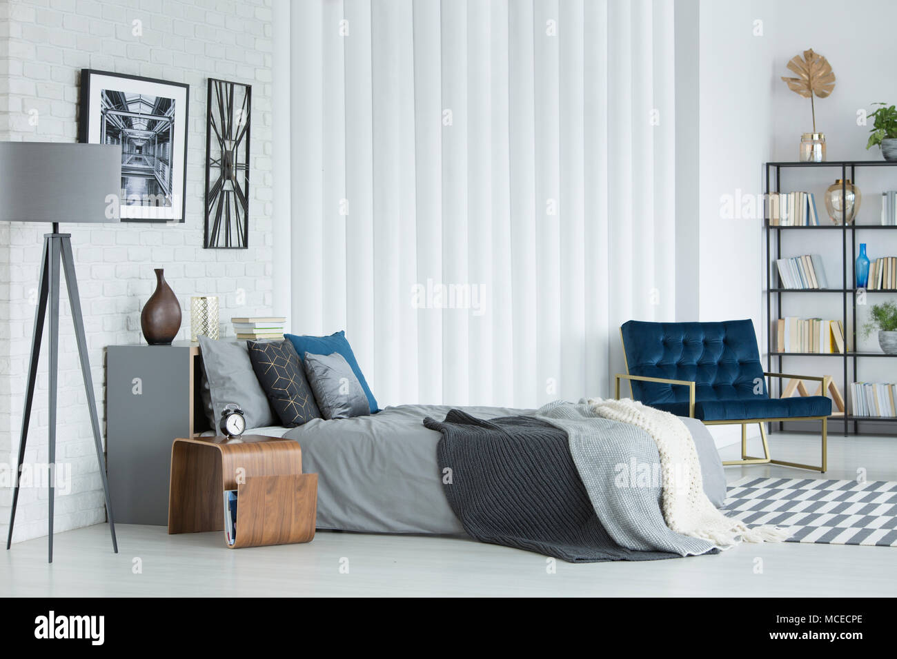 Grey lamp next to bed against white wall with poster and clock in ...