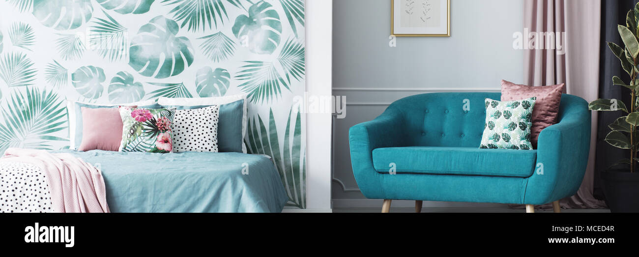 Header of an open space living room and bedroom interior with floral cushions and leaves pattern wallpaper Stock Photo