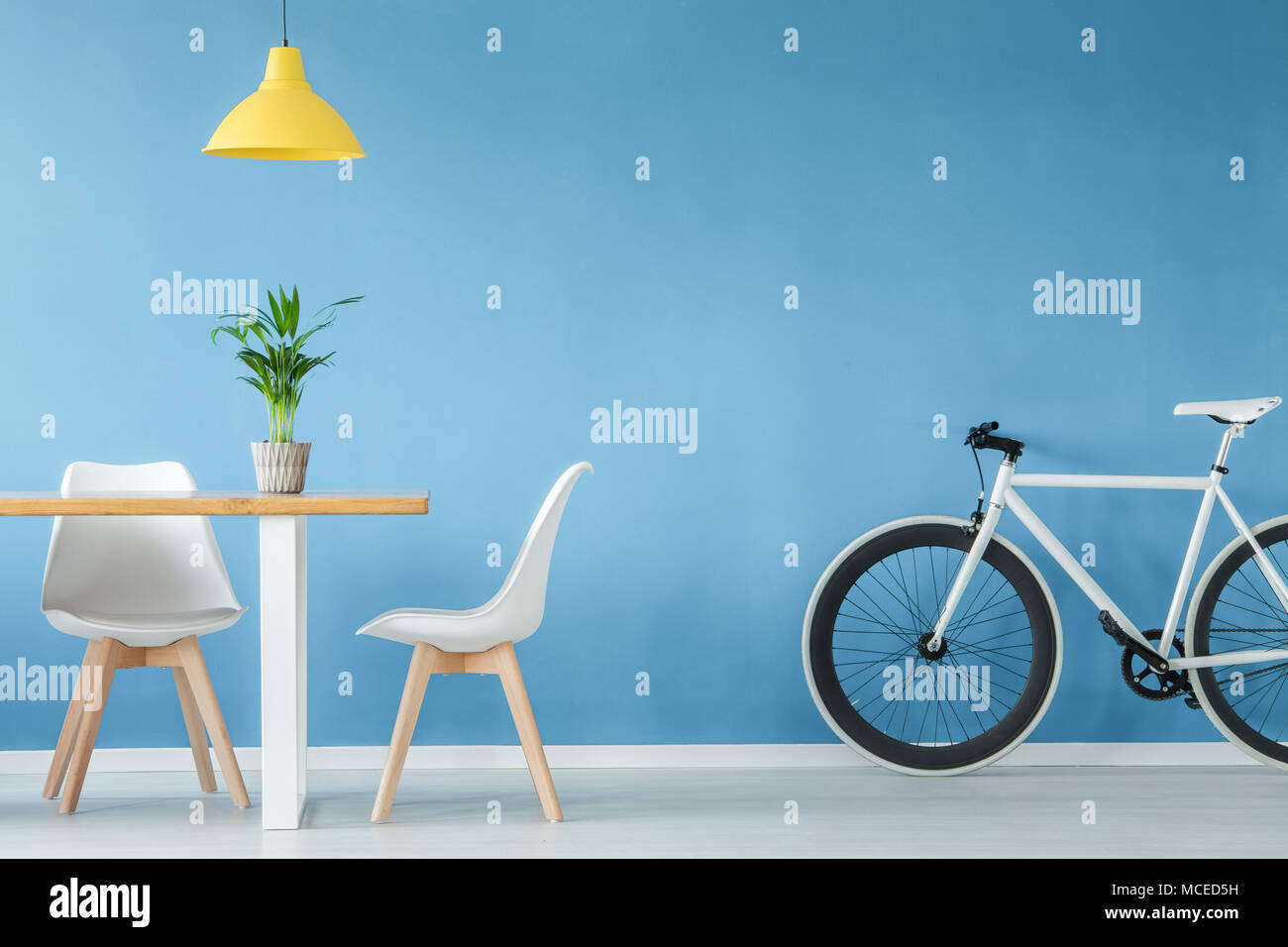 Minimal, modern interior with two chairs, a bicycle, a table with a plant on it and a yellow lamp above, against blue wall - Stock Image