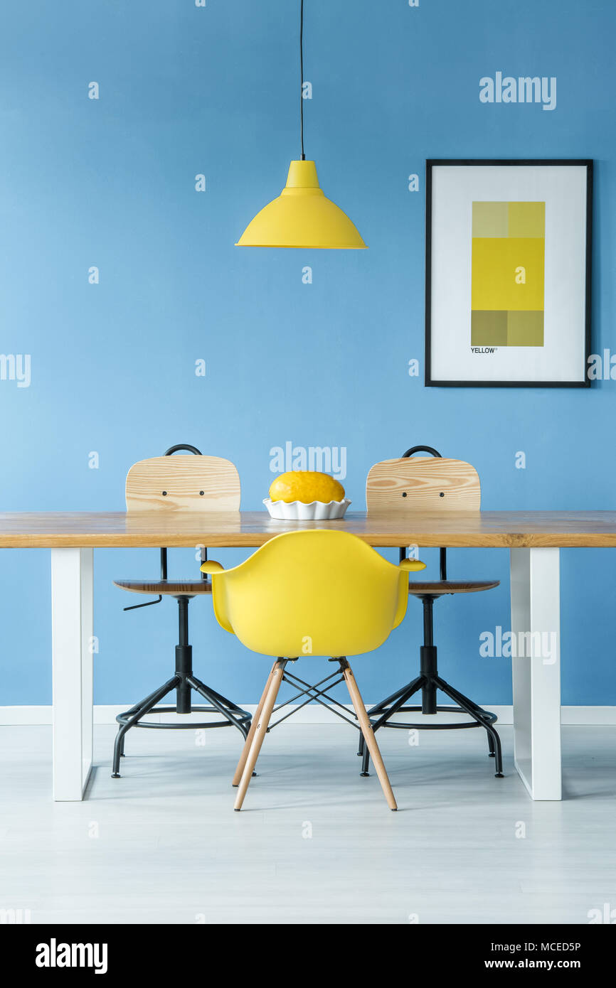 Minimal style symmetric interior with a yellow lamp hanging over a wooden table with a melon in a dish, chairs and a poster on a blue wall - Stock Image