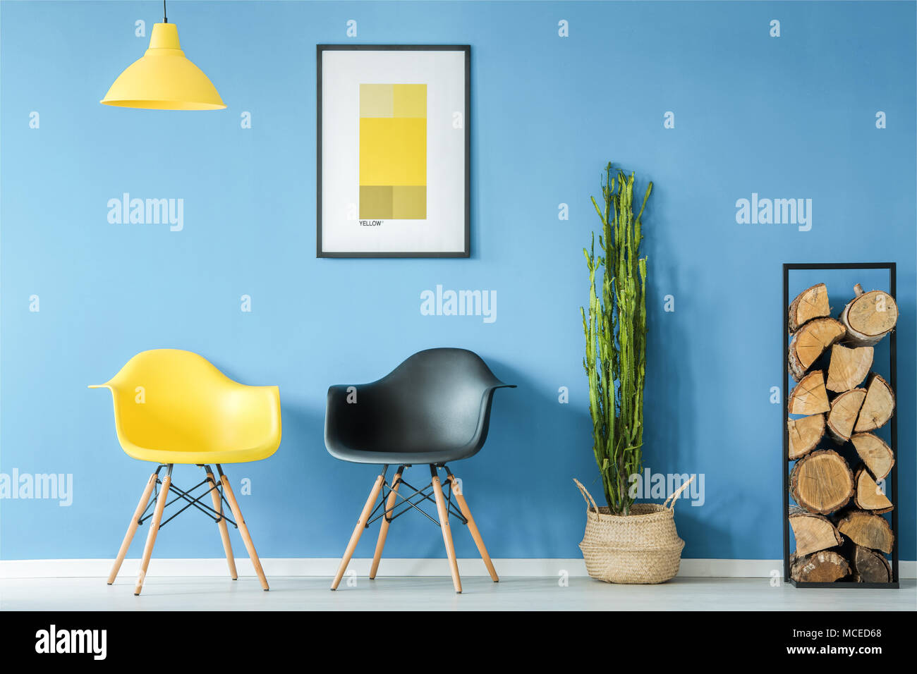 Waiting room interior in minimal style with contrasting yellow and black chairs, lamp, firewood, plant in a pot and a poster on a blue wall - Stock Image