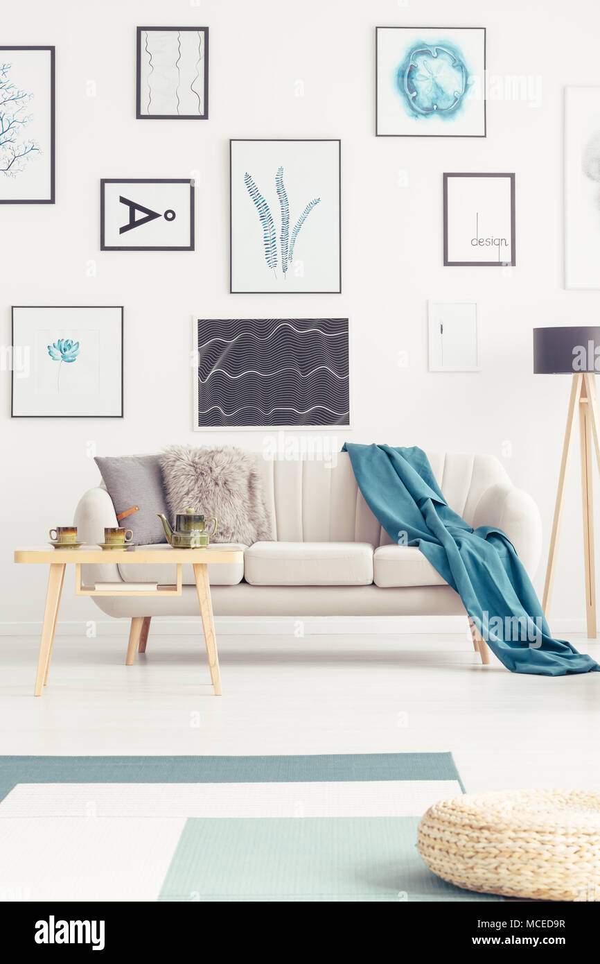 Blue Blanket On Beige Sofa Against White Wall With Posters In Living Room  Interior With Pouf