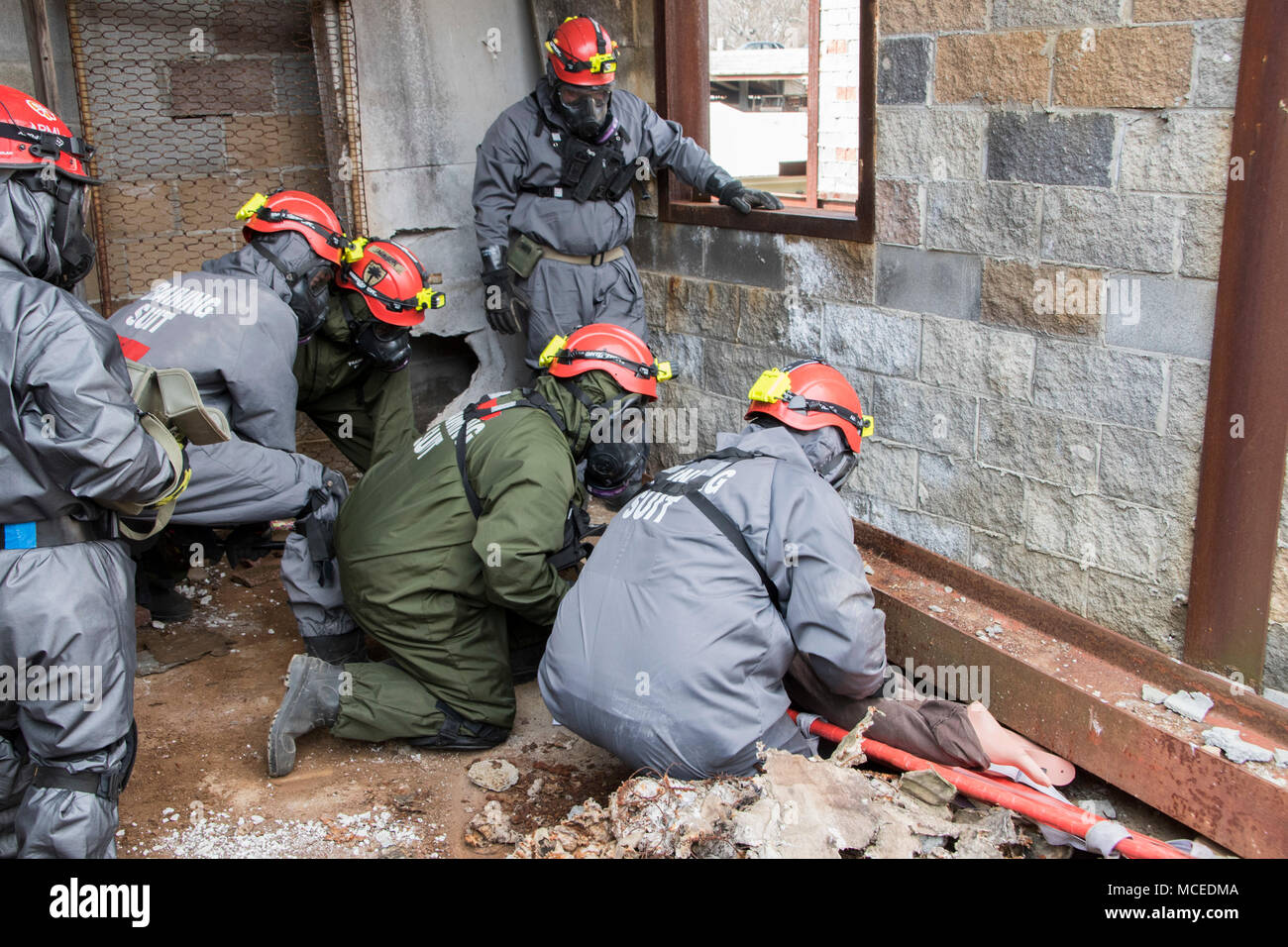 Soldiers from the 267th Engineer Detachment (Fire Fighters), South Carolina Army National Guard, work together to free a simulated casualty that was trapped under a steel beam in a simulated collapsed building during a urban search and rescue drill as a part of Exercise Guardian Response, April 13, 2018, at Muscatatuck Urban Training Center, Butlerville, Indiana. The 267th, based in Eastover, South Carolina, worked with Army National Guard search and resuce teams from Alabama, Florida and Maryland to locate and evacuate simulated casualties in the building during the exercise. (U.S. Army photo - Stock Image