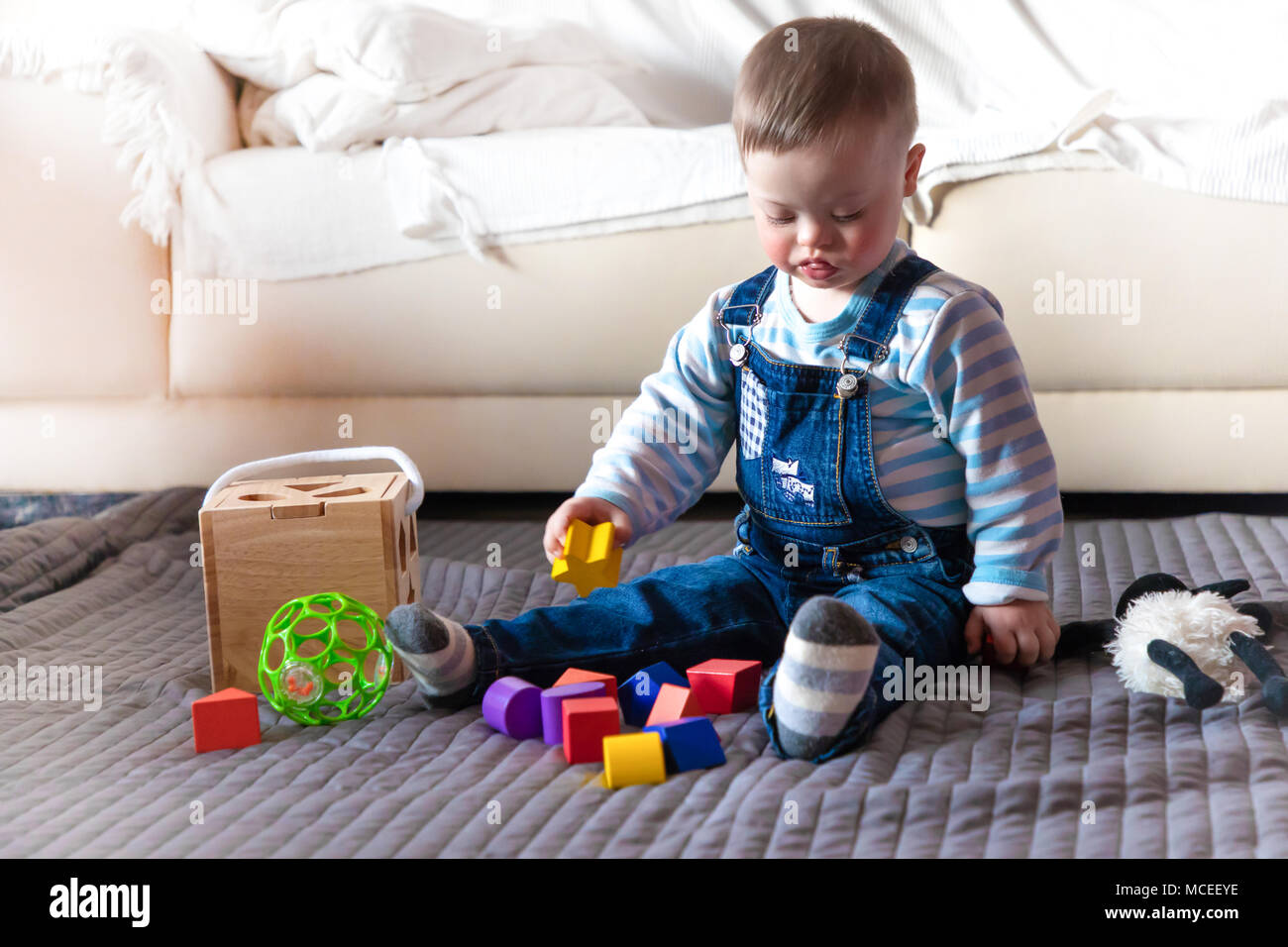 Portrait of cute baby boy with Down syndrome - Stock Image