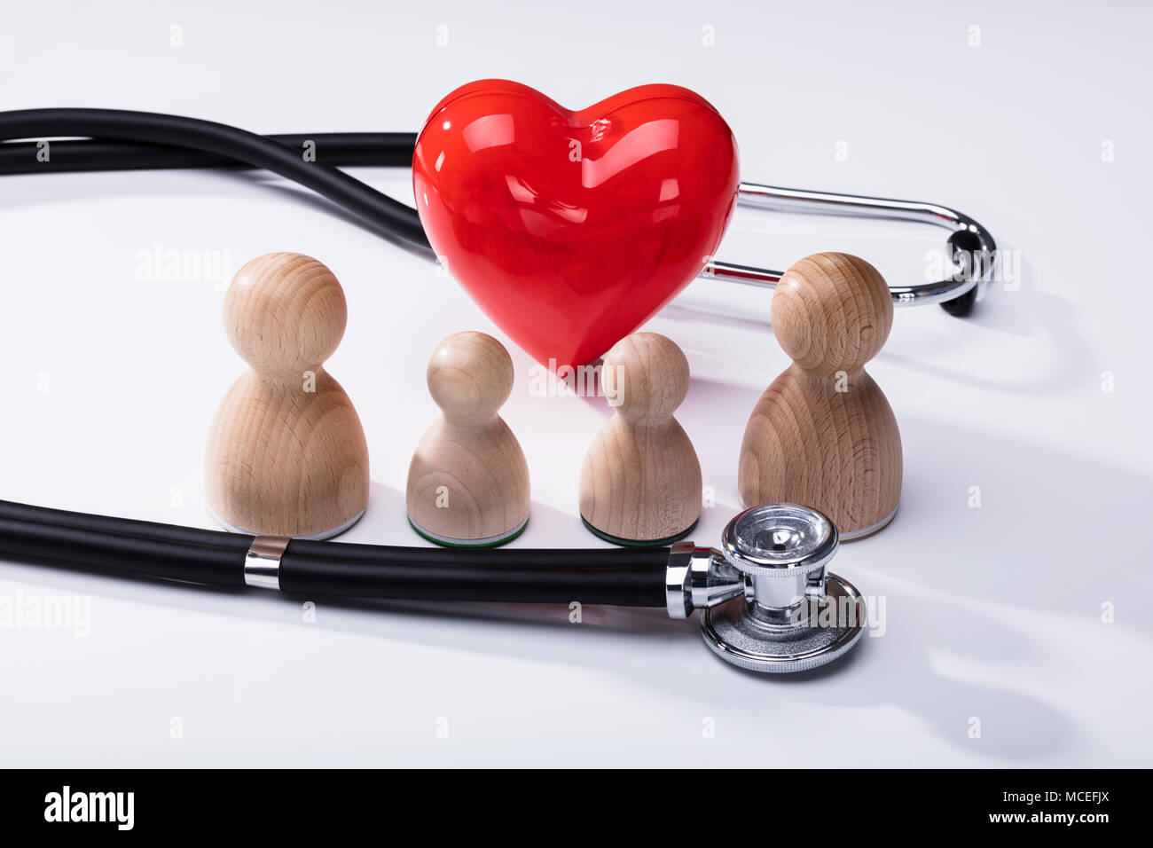 Close-up Of Wooden Pawns, Red Heart Shape And Stethoscope On White Background - Stock Image