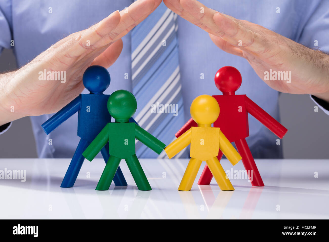 Close-up Of A Human Hand Protecting Multi Colored Human Figures On White Desk Stock Photo