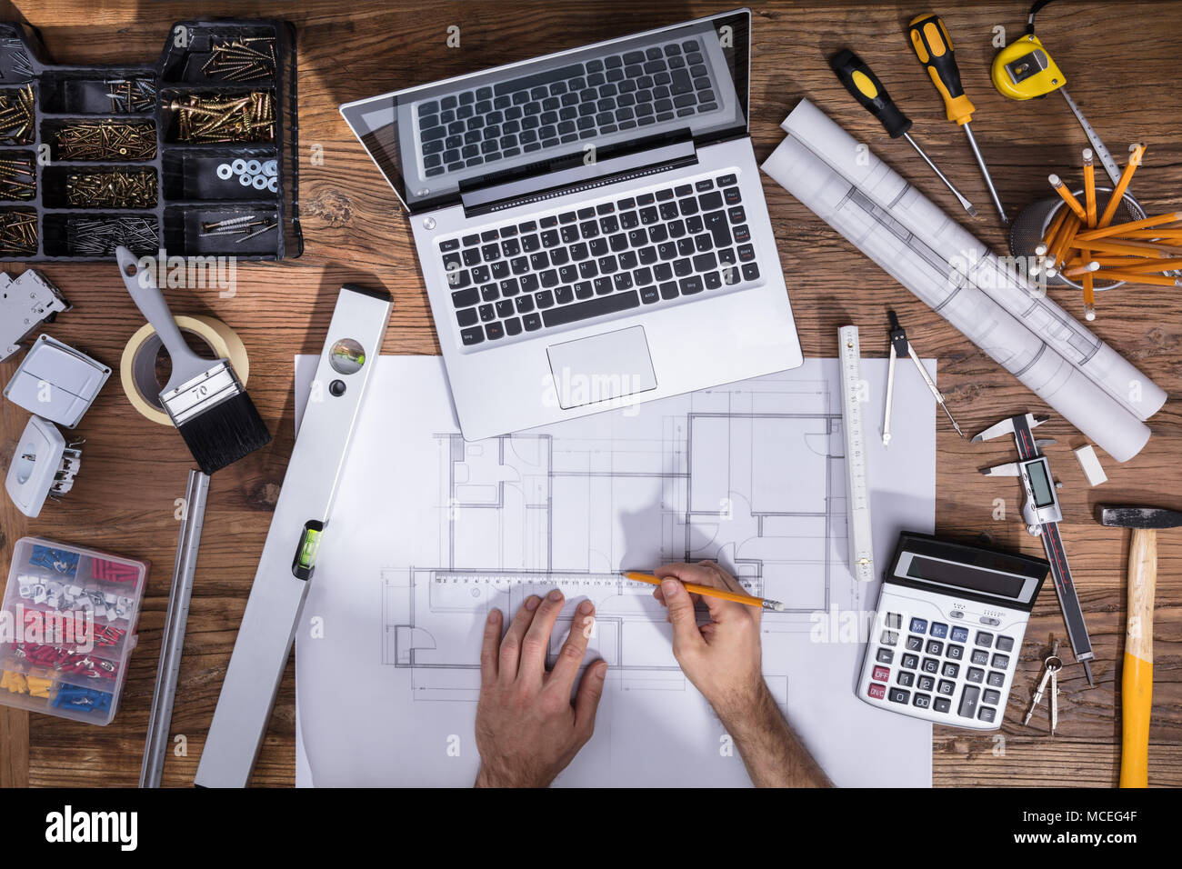 Architecture's Hand Drawing Blueprint With Laptop On Wooden Desk - Stock Image