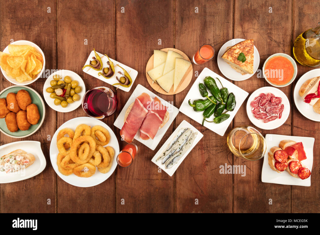 An overhead photo of an assortment of Spanish tapas food, shot from the top on a dark rustic background with a place for text. Jamon, gazpacho, cheese - Stock Image