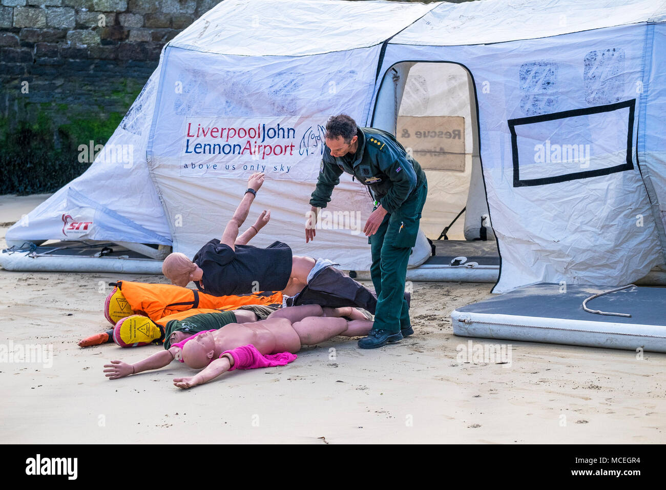 A paramedic using mannequins in preparation for use in a GMICE (Good Medicine in Challenging Environments) major incident exercise in Newquay Harbour  - Stock Image