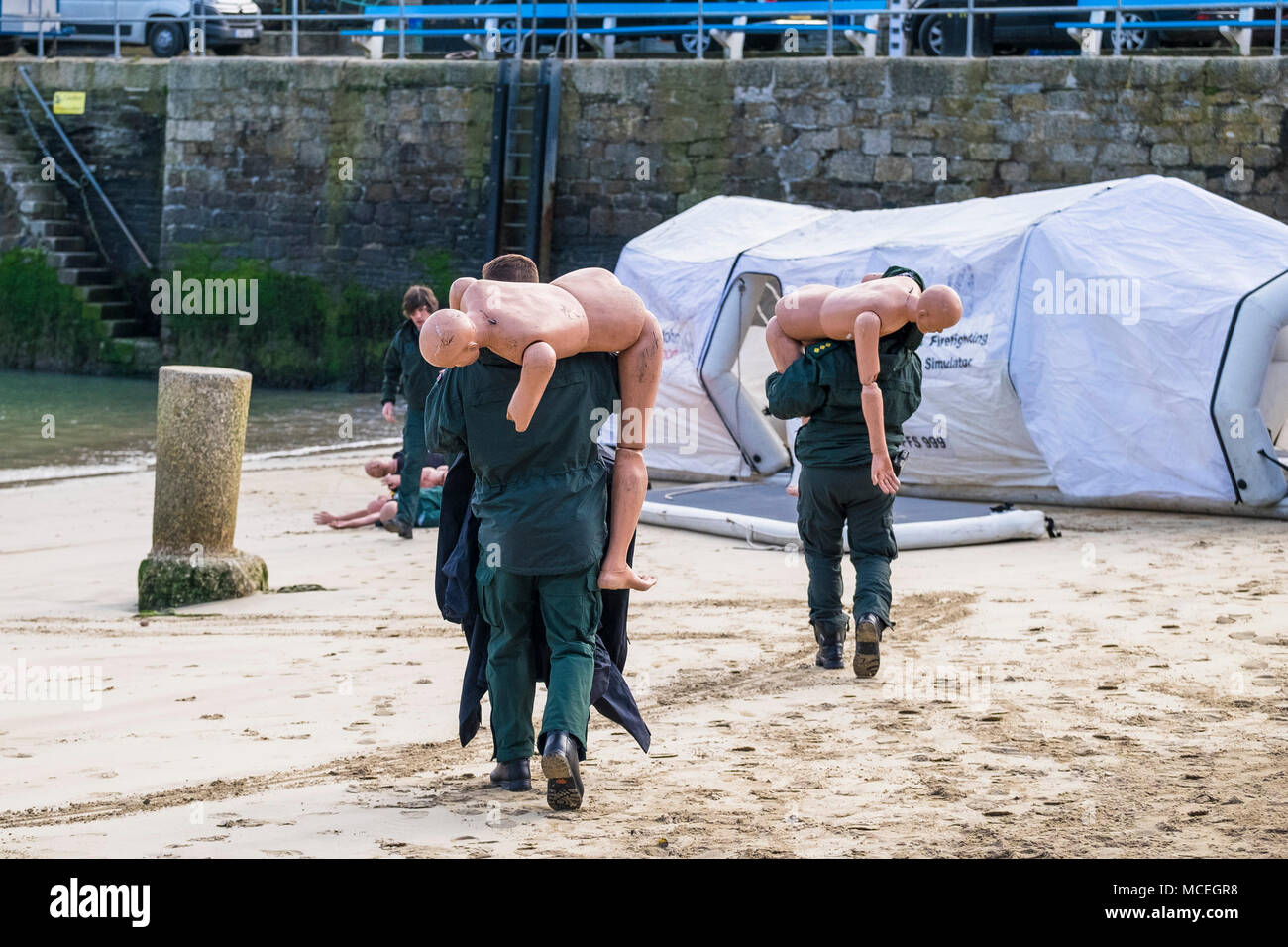 Paramedics carrying mannequins in preparation for use in a GMICE major incident exercise in Newquay Harbour in Cornwall. - Stock Image