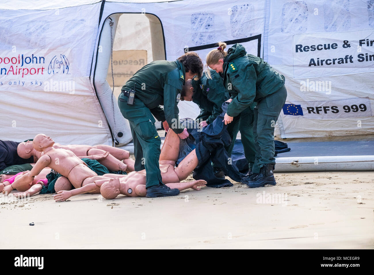 Paramedics dressing mannequins in preparation for use in a GMICE major incident exercise in Newquay Harbour in Cornwall. - Stock Image