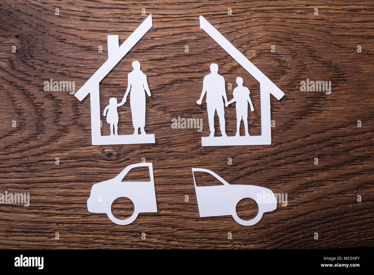 White Paper Cutout Of A Family Split Apart With Car On Wooden Background - Stock Image