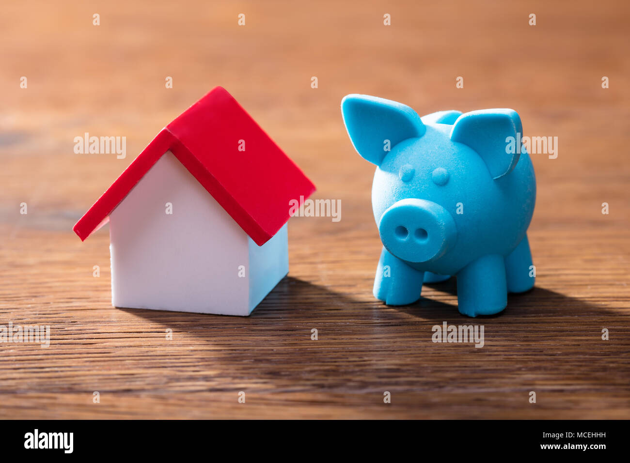 Close-up Of House Model And Blue Piggybank On The Wooden Table - Stock Image