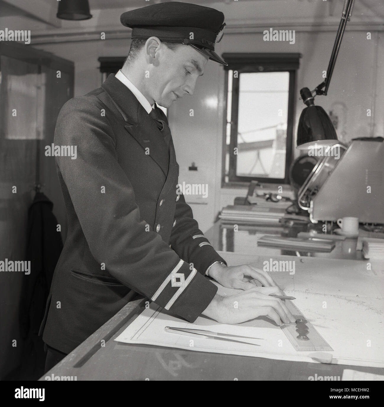 1950s, historical, second officer or navigator in his uniform onboard the deck of a steamship, working on the navigational charts to establish the ship's exact position. - Stock Image