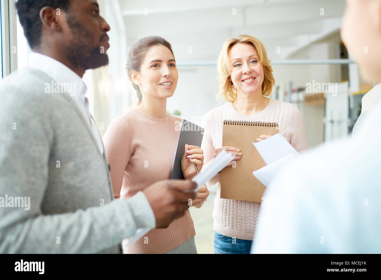 Enthusiastic team of managers holding clipboards and documents in hands while having productive project discussion at spacious open plan office - Stock Image