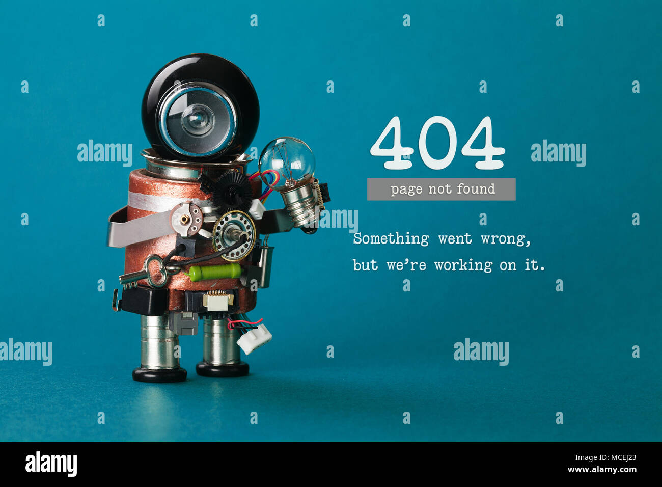 404 error web page not found. Futuristic robotic toy mechanism, black helmet head, light bulb in hand. Blue background. Text something went wrong but we are working on it. - Stock Image
