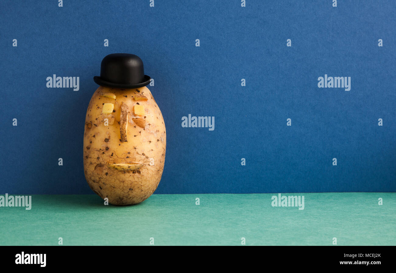 Senor Potato bowler hat serious face. Old fashioned style vegetable on blue wall green floor background. Copy space. - Stock Image