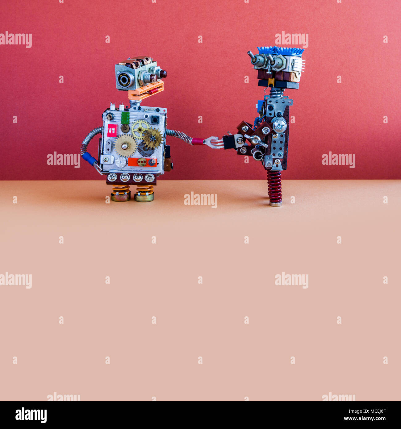 Two robots greet each other. Handshake of cybernetic mechanical cyborgs. Creative design robotic toys, red wall brown floor background. Copy space - Stock Image