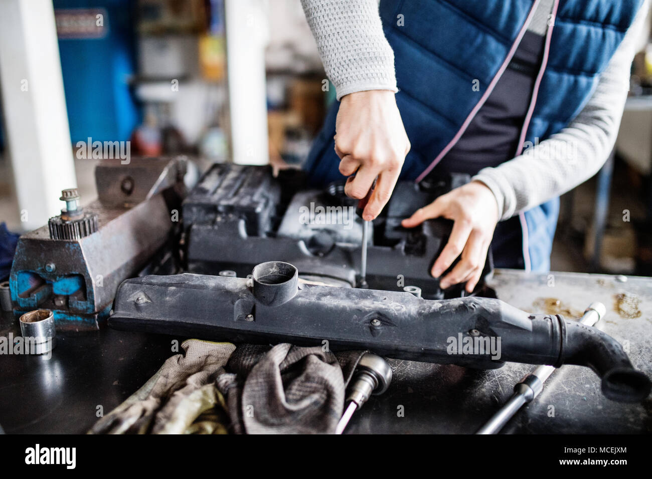 Man mechanic repairing a car in a garage. - Stock Image