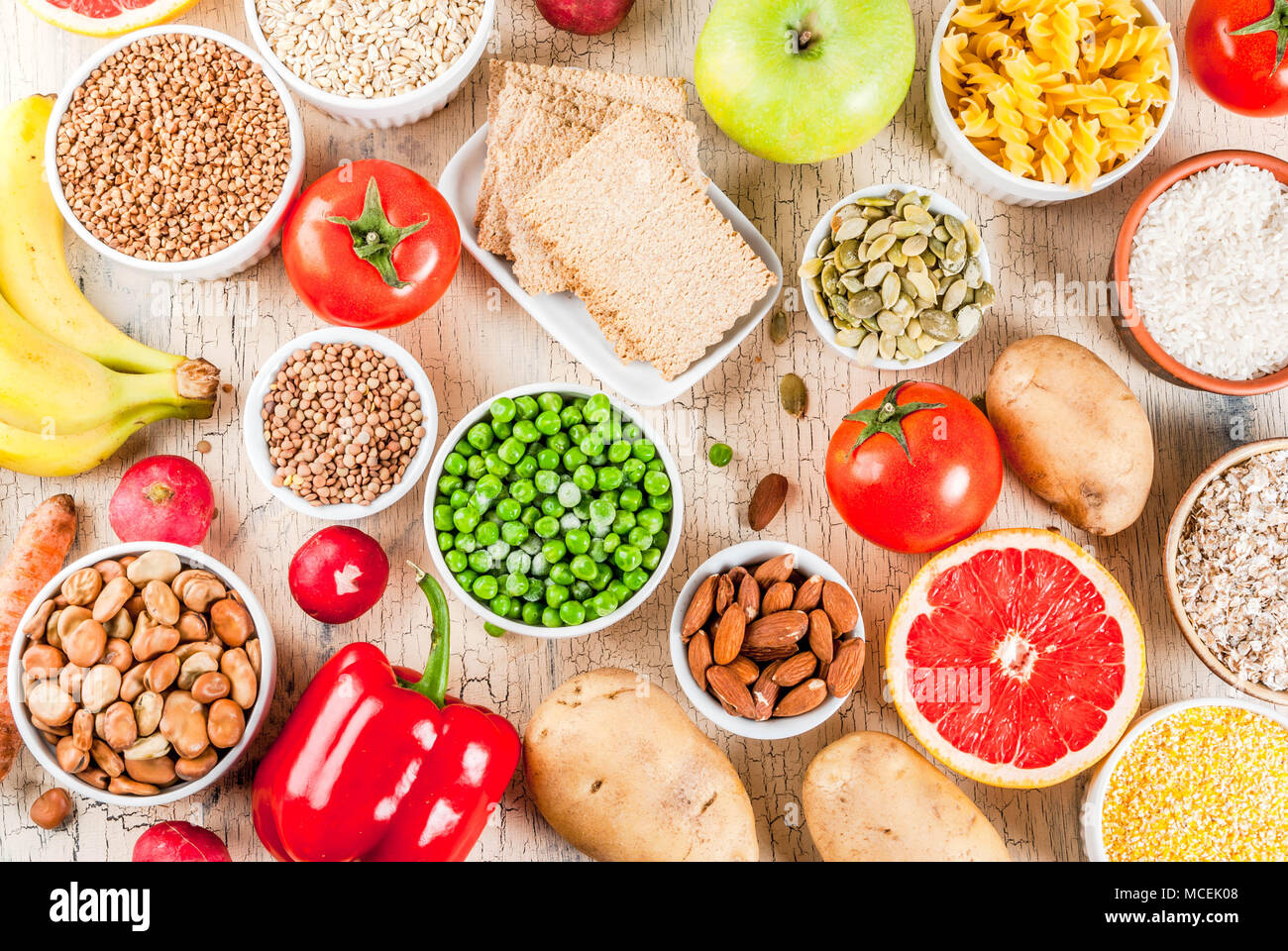 Diet food background concept, healthy carbohydrates (carbs) products - fruits, vegetables, cereals, nuts, beans, light concrete background above - Stock Image