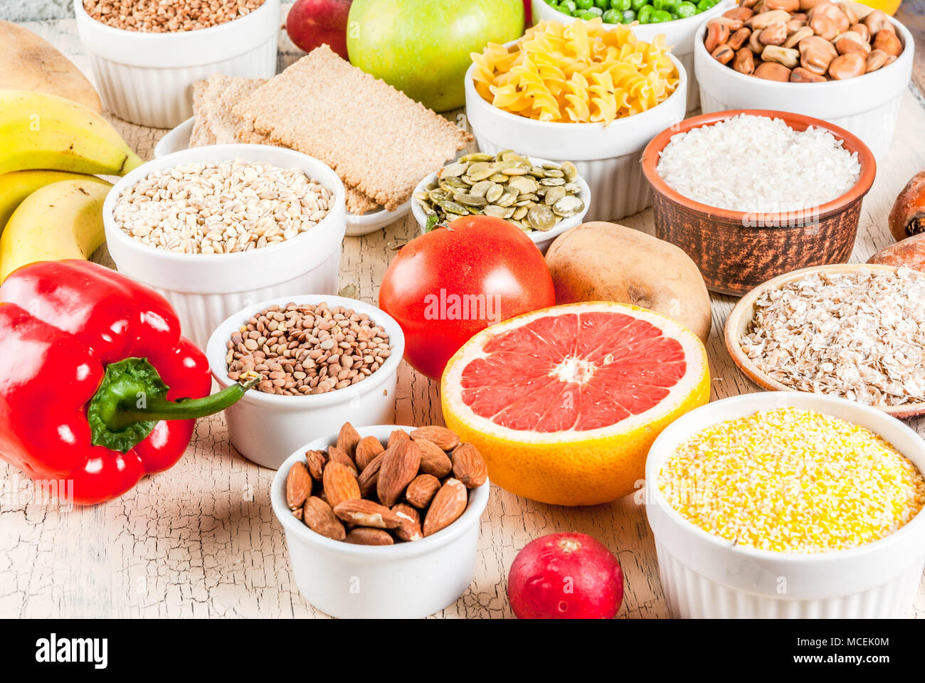 Diet food background concept, healthy carbohydrates (carbs) products - fruits, vegetables, cereals, nuts, beans, light concrete background - Stock Image