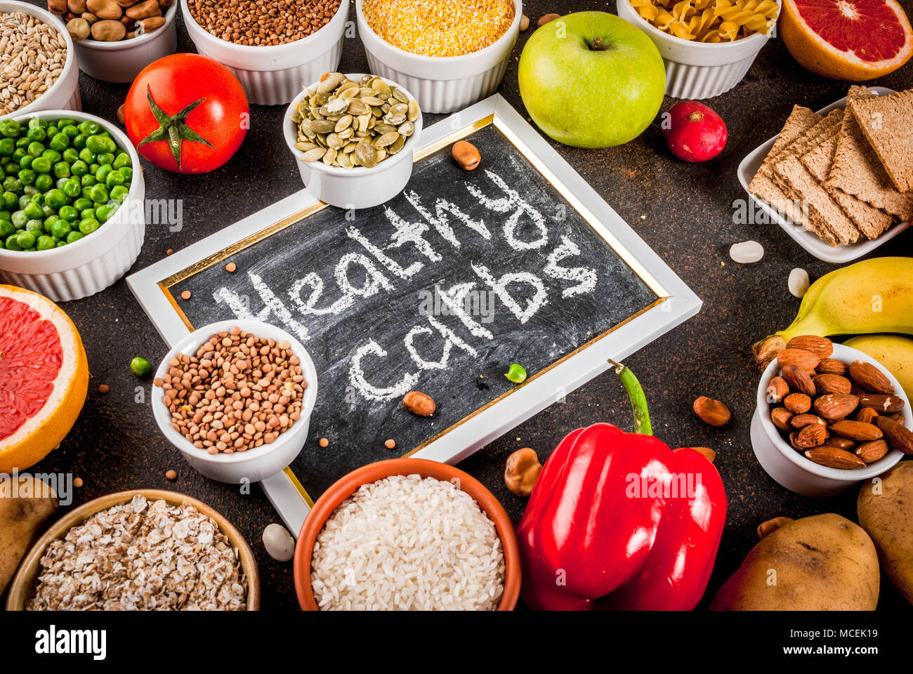 Diet food background concept, healthy carbohydrates (carbs) products - fruits, vegetables, cereals, nuts, beans, dark blue concrete background - Stock Image