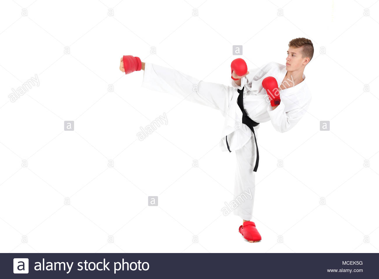 Young karate fighter in front of white background - Stock Image