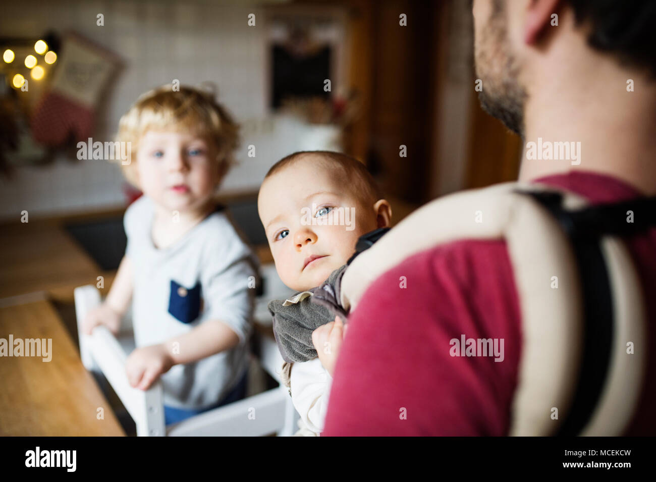 Father with two toddlers at home. - Stock Image