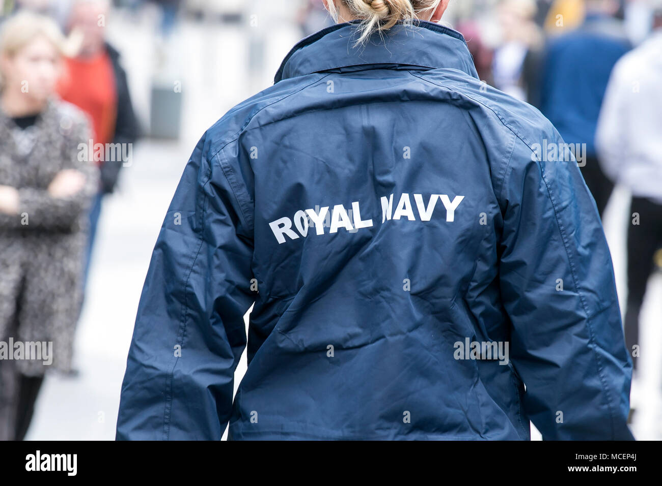 A female royal navy sailor wearing uniform with royal navy logo from rear view - Stock Image