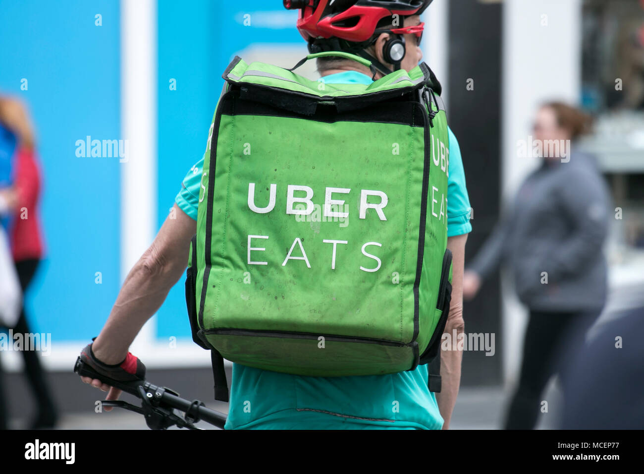 Uber eats take away food delivery smartphone online order cyclist delivering - Stock Image