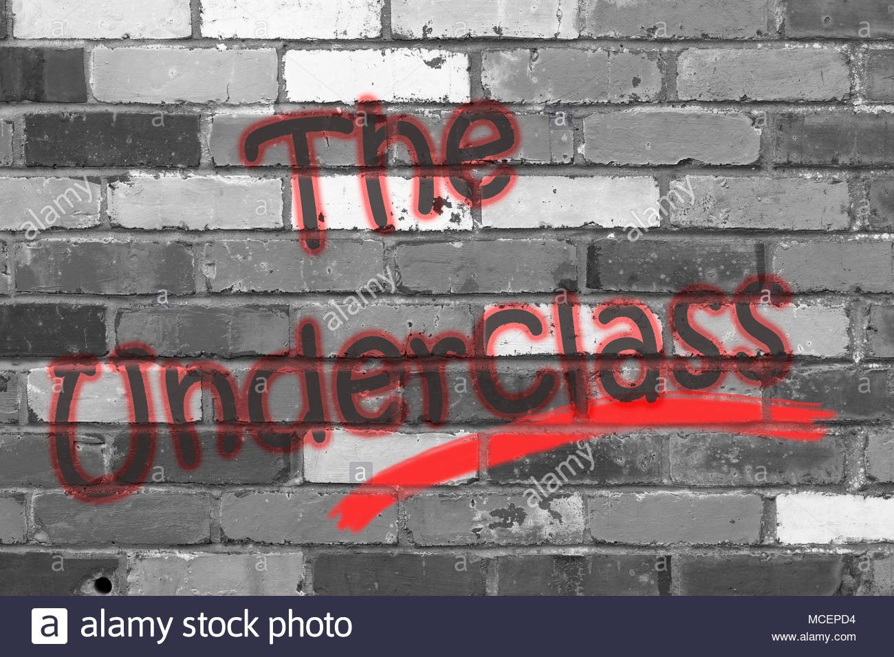 Looking at a black and white brickwall with the wording The Underclass. Dorset, England - Stock Image
