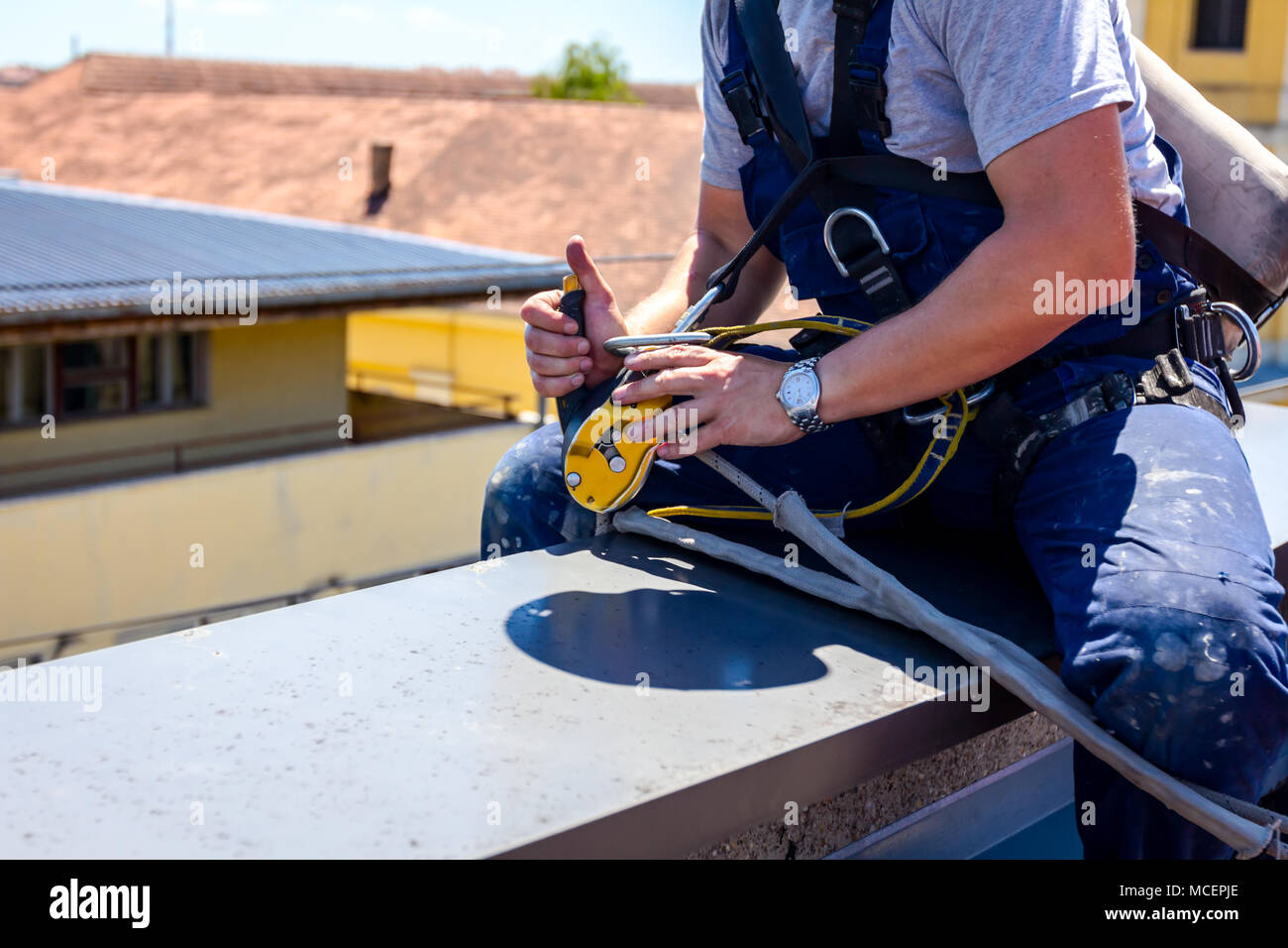 Industrial climber, alpinist, is adjusting climbing gear, preparing safety ropes. - Stock Image
