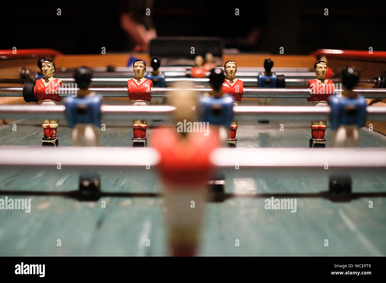 close up shot of a metal players on a vintage table football table - Stock Image