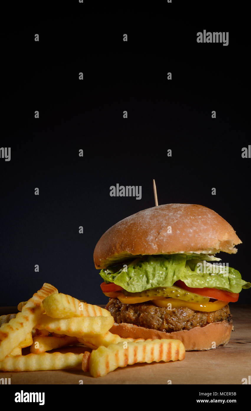 Burger & Fries with dark background space - Stock Image