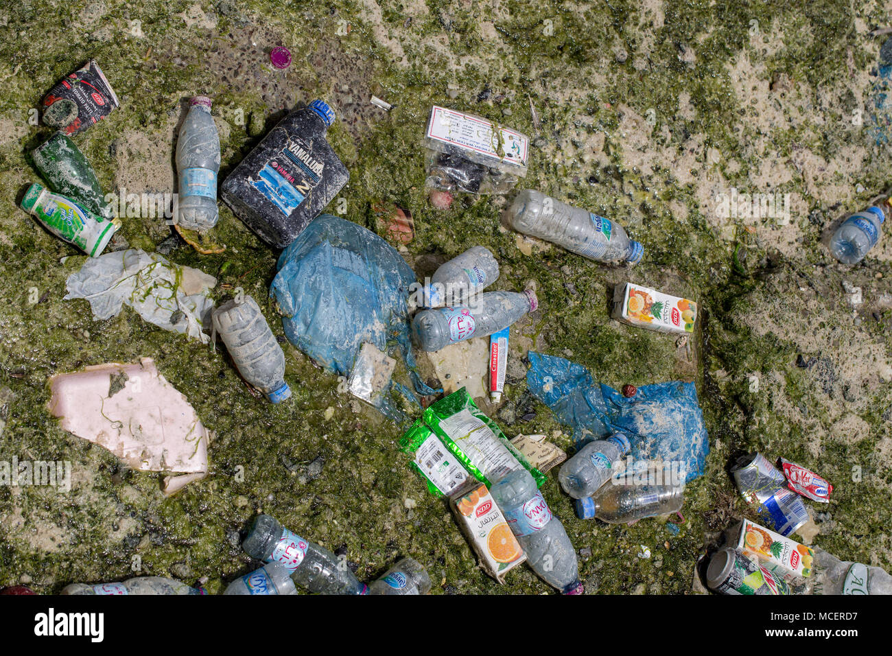 DOHA BAY, QATAR - April 16, 2018: Detritus left behind in Doha Bay, Qatar, by the outgoing tide - a mixture of plastic, metal and paper - Stock Image
