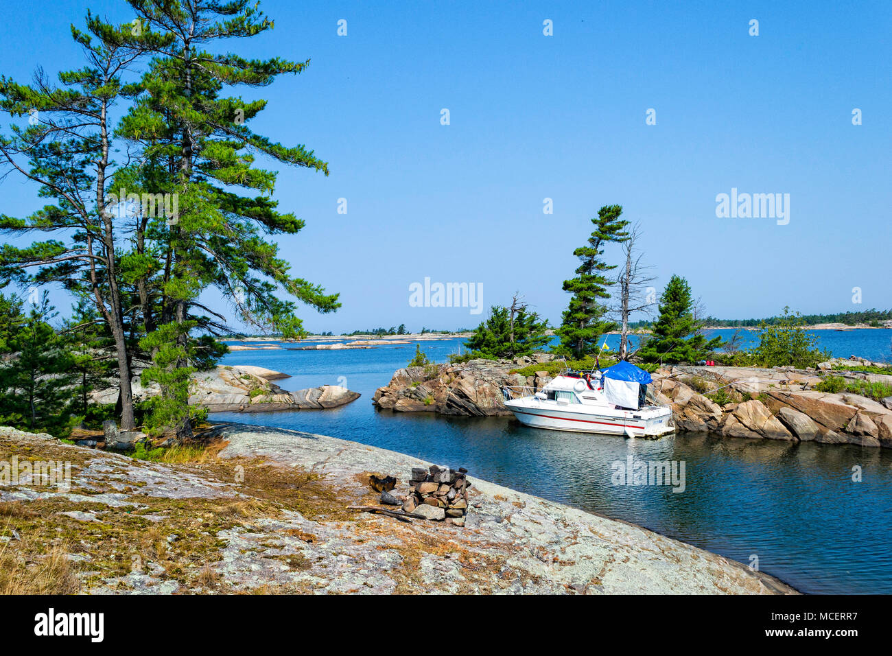 A boat tied to a rock wall in Georgian Bay - Stock Image