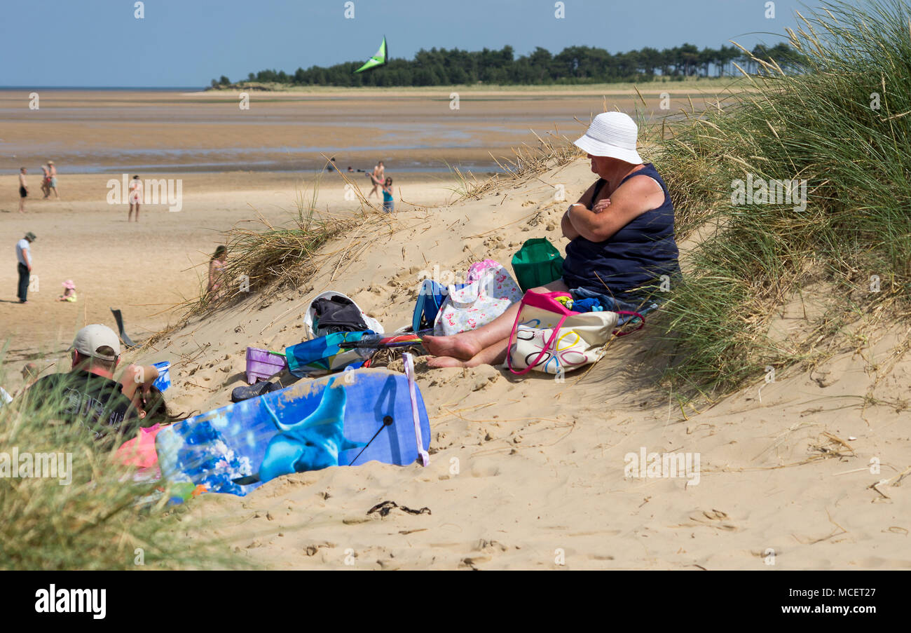 A woman sitting on a sand dune reading a book - Stock Image