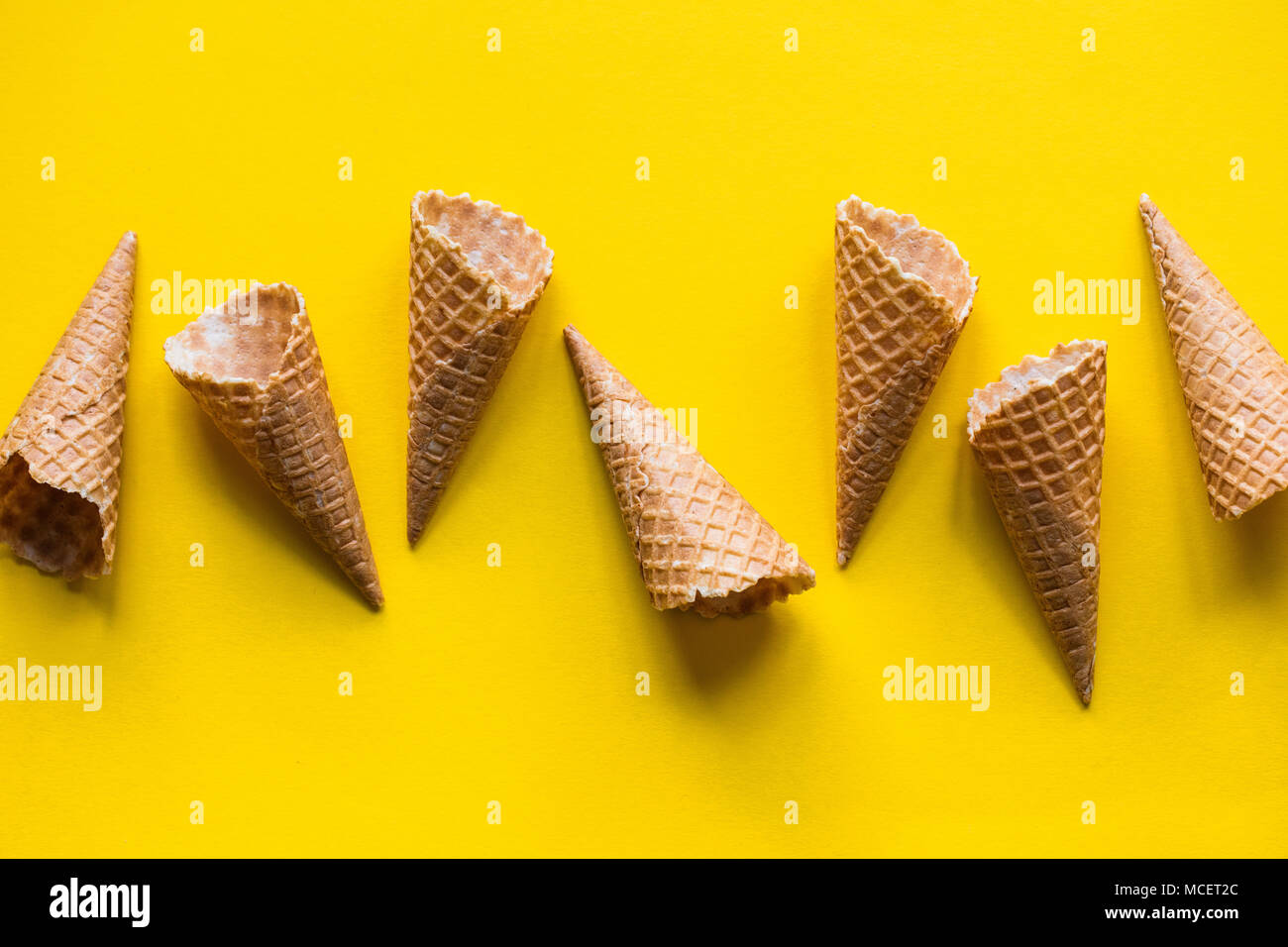 Empty waffle wafer ice cream cone on a bright yellow background - Stock Image